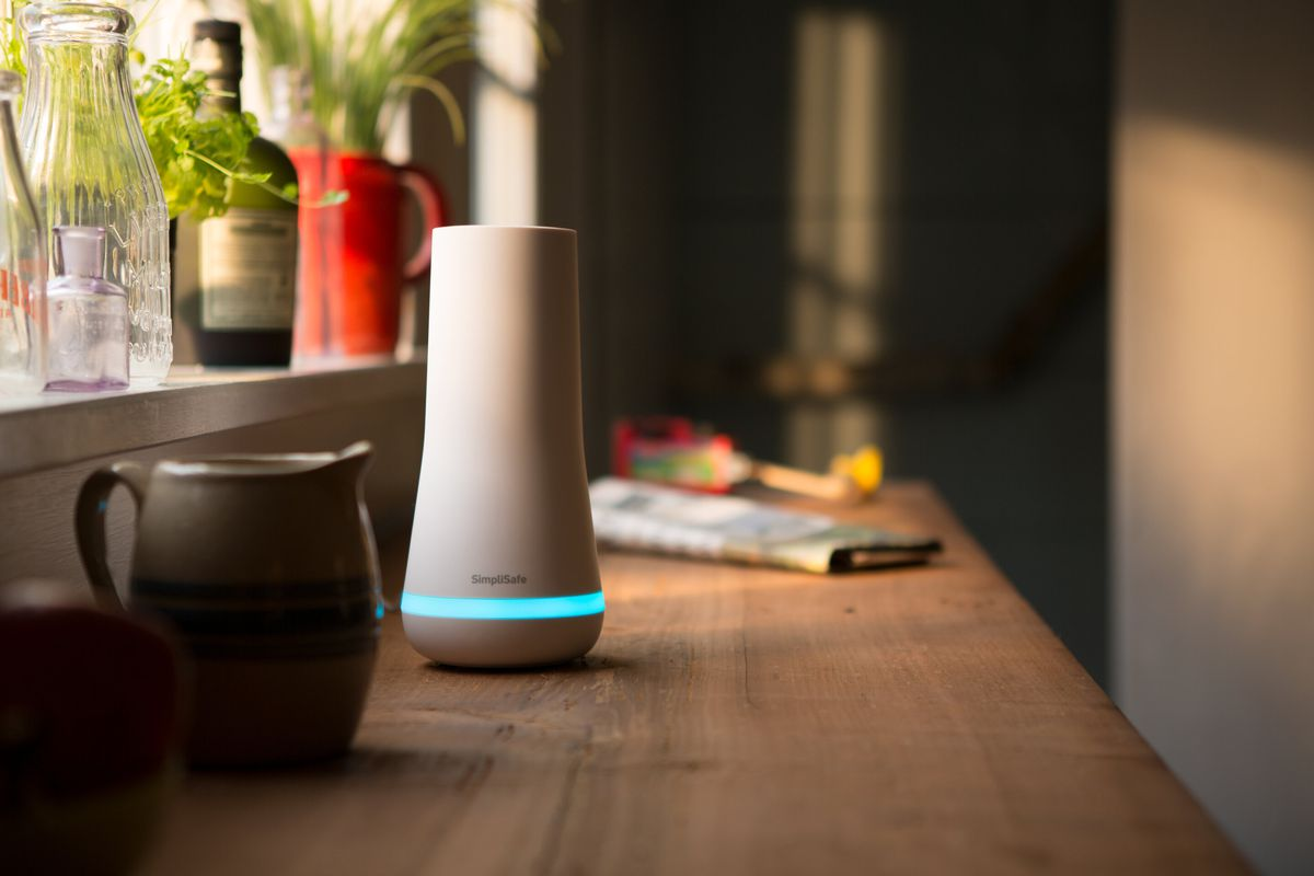 A SimpliSafe security system sits on a wooden ledge in the interior of a home.