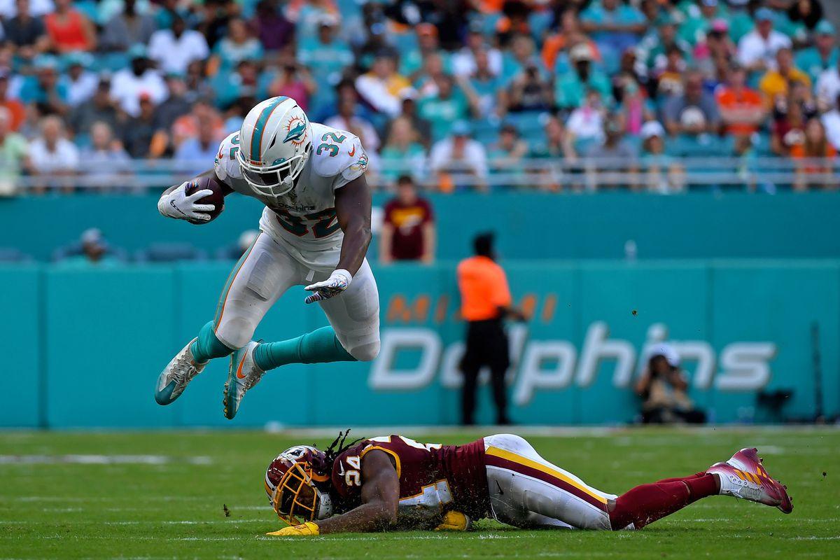 Miami Dolphins running back Kenyan Drake leaps over Washington cornerback Josh Norman during the second half at Hard Rock Stadium.