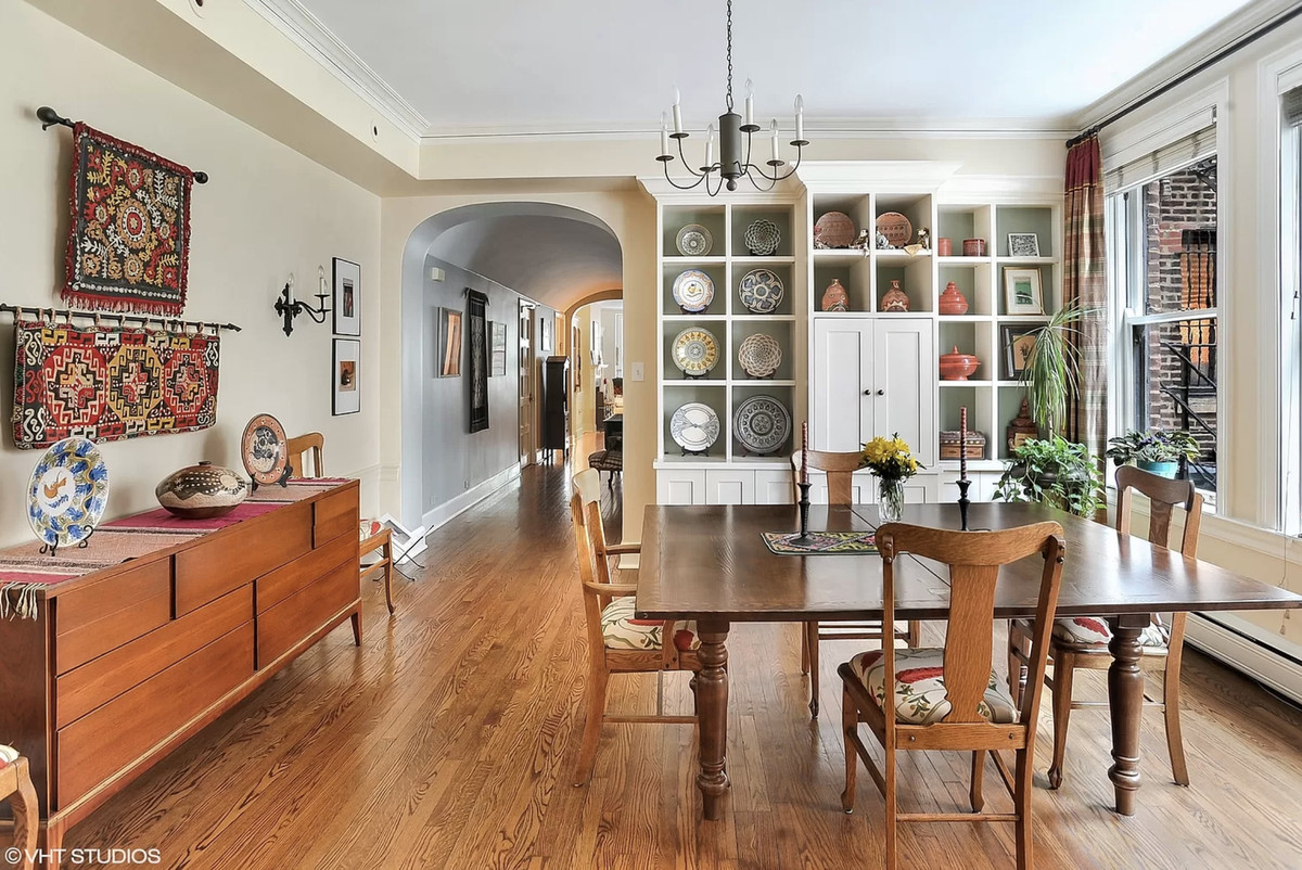 A photo of a formal dining room. There is a table with four chairs, built-in cabinets displaying ceramics, and a credenza opposite the windows.