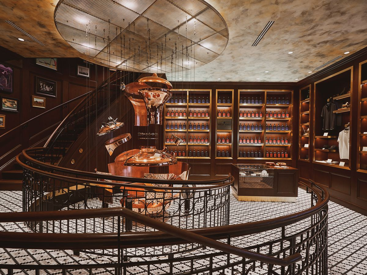 A indoor room with a spiral staircase and dark wooden floor-to-ceiling shelves showcasing bottles of whiskey.