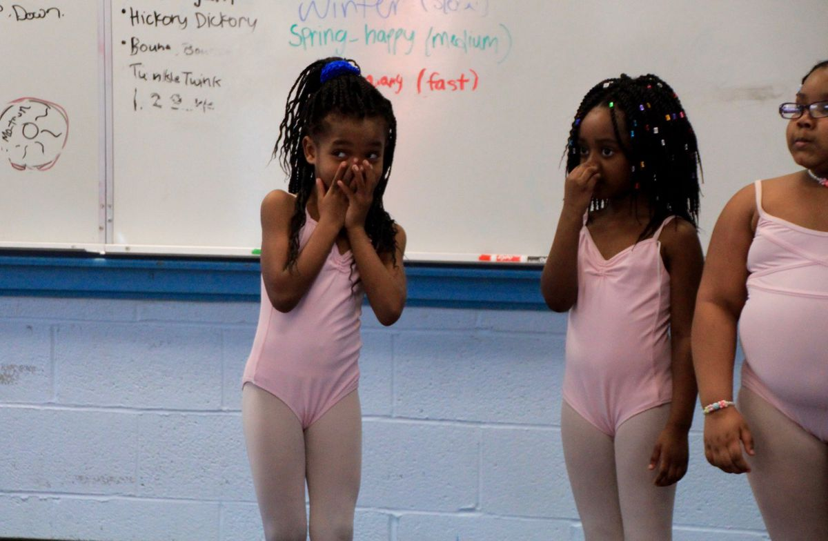 Youngsters giggle as they watch their instructor demonstratea dance move.