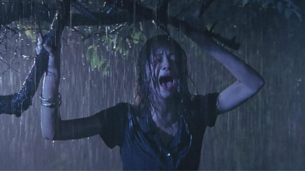 A woman wailing as she's drenched in a downpour of rain