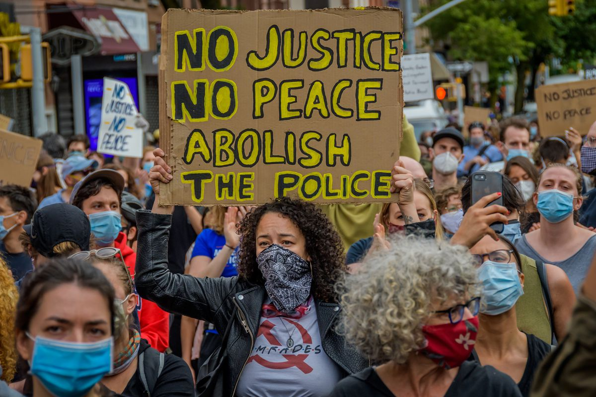 """A protestor holding a sign that reads, """"No justice, no peace, abolish the police"""""""