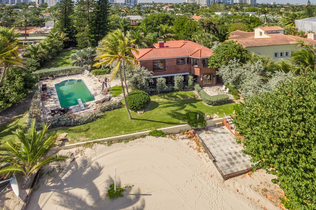Aerial of a beachfront home with a red roof, private beach and a pool