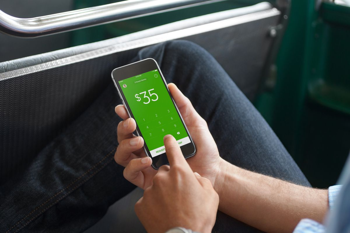 A person holds a smartphone that shows the Square Cash app on the screen.