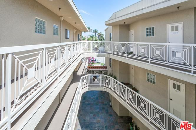 The exterior of a courtyard-style complex clad in beige stucco with geometric white railings.