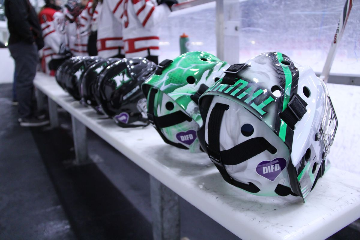 Helmets of the Markham Thunder sit on the bench with the green-and-white painted goalie helmets closest to the camera