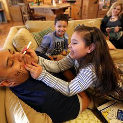 Kalani Sitake gives in as his daughter Sadie draws on him at home in Provo on Friday, March 11, 2016. His son KK and wife Timberly watch in the background.