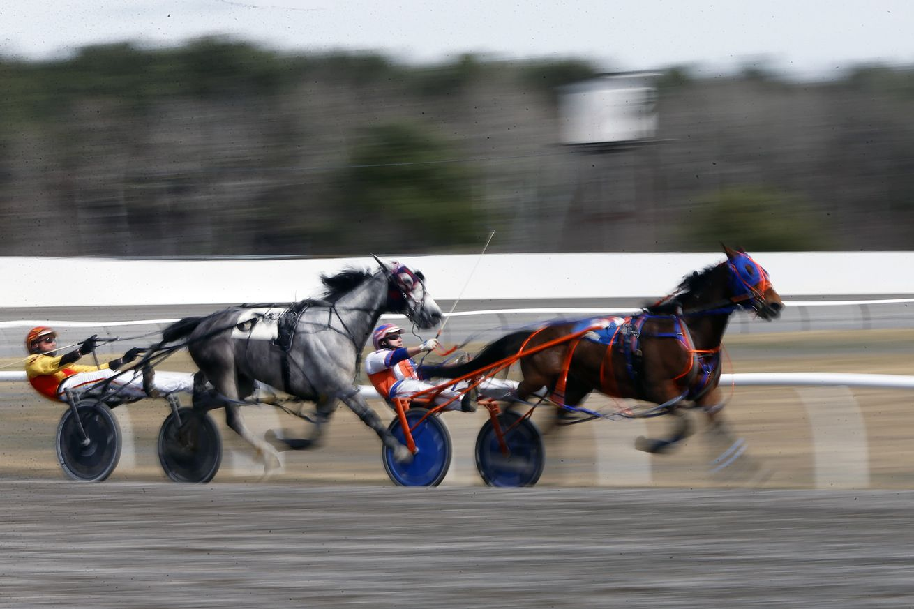 Two horses race down the home stretch of Scarborough Downs towards the finish line