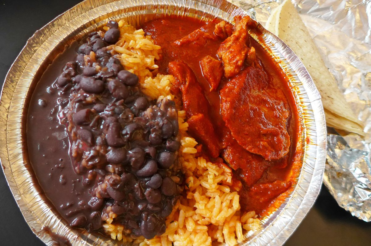 A thick red stew with pork, yellow rice, and black beans in three parallel bands.