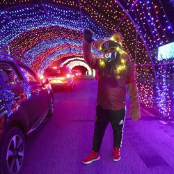 """Leo the Lion, RSL's mascot, waves to people driving through """"Light the RioT,"""" a drive-thru light show, outsideRio Tinto Stadium in Sandy on Monday, May 4, 2020."""