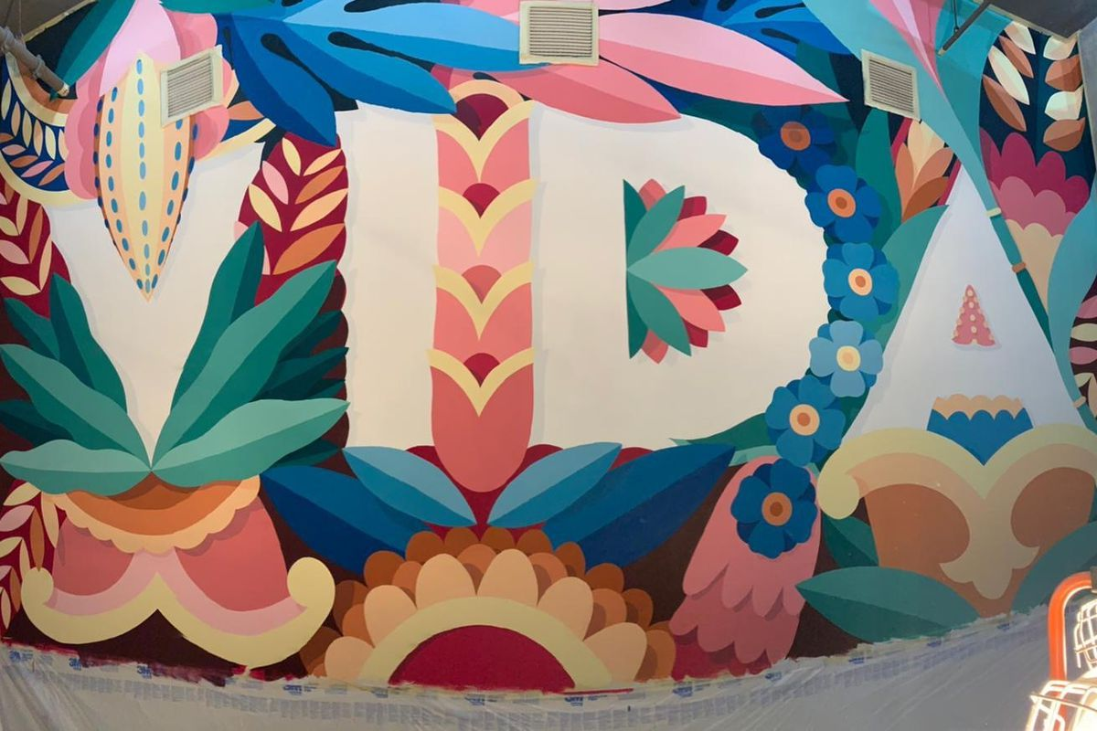"An unfinished mural with the word ""Vida"" surrounded by tropical flowers and plants"