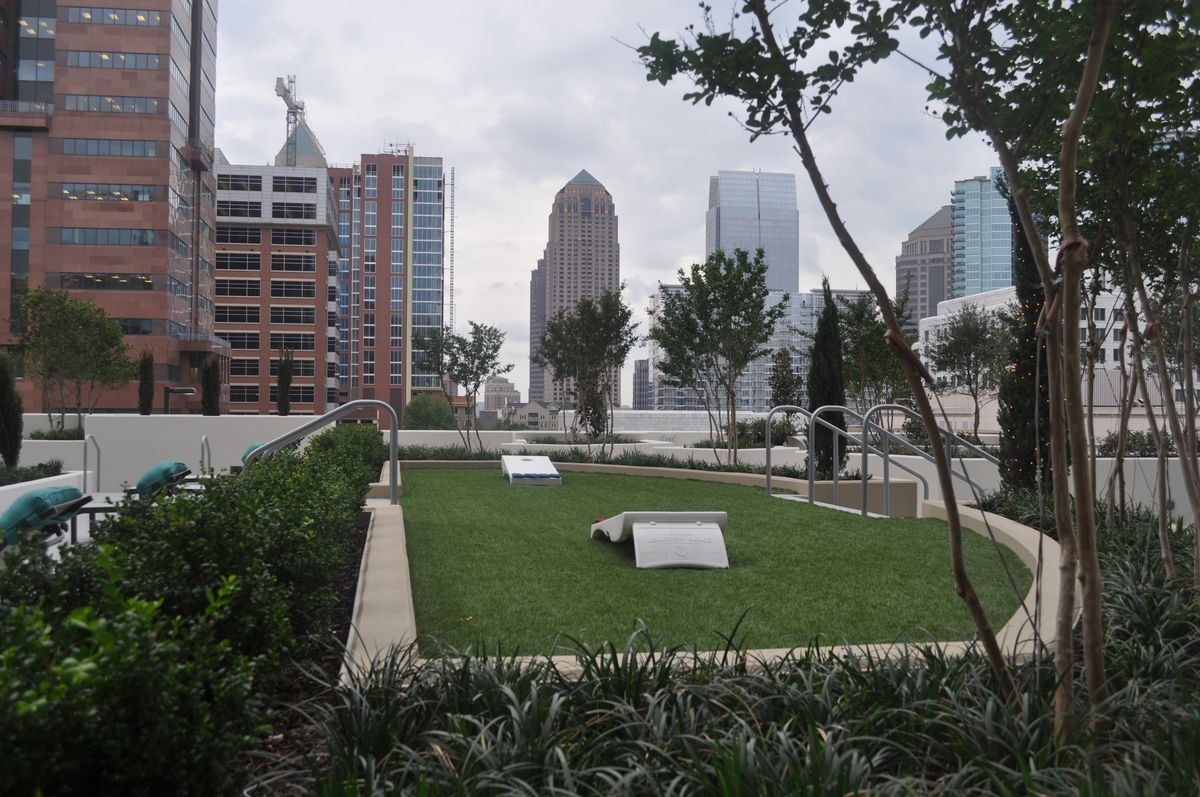 A grass strip is set up for cornhole, with the Midtown skyline just beyond.