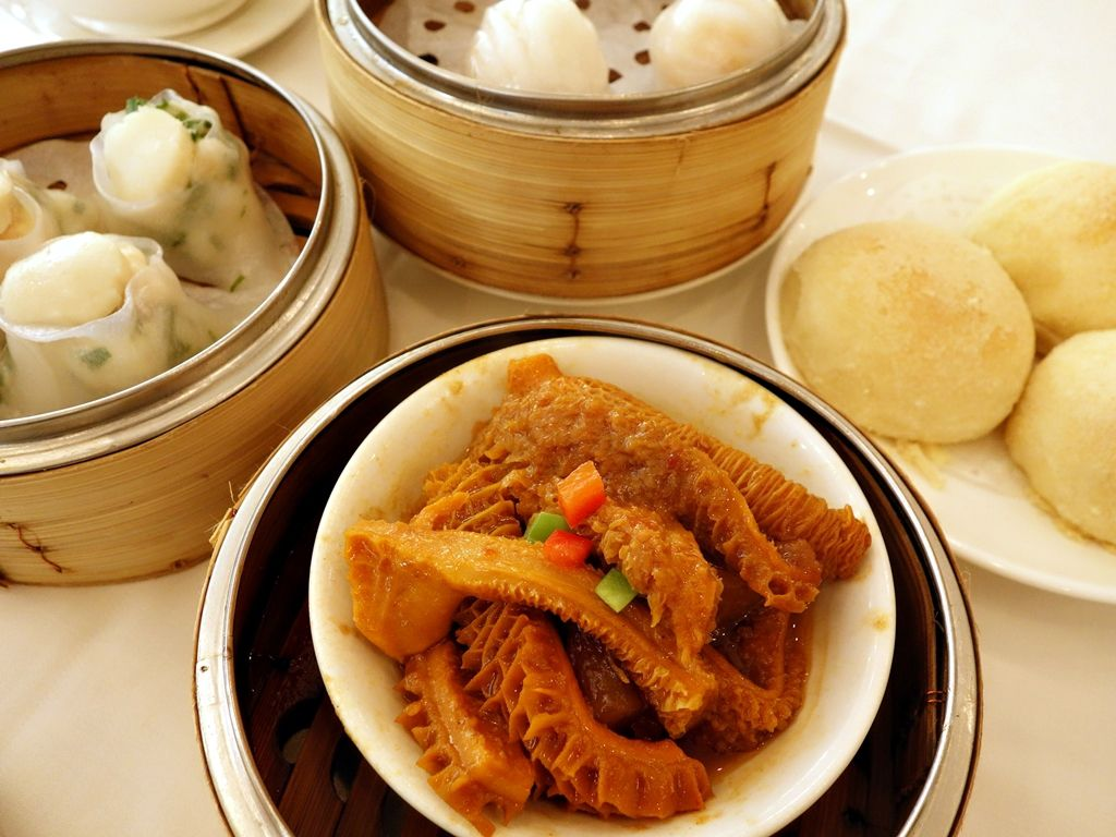 Steamer baskets of dumplings beside a plate of steam buns and a plate of tripe