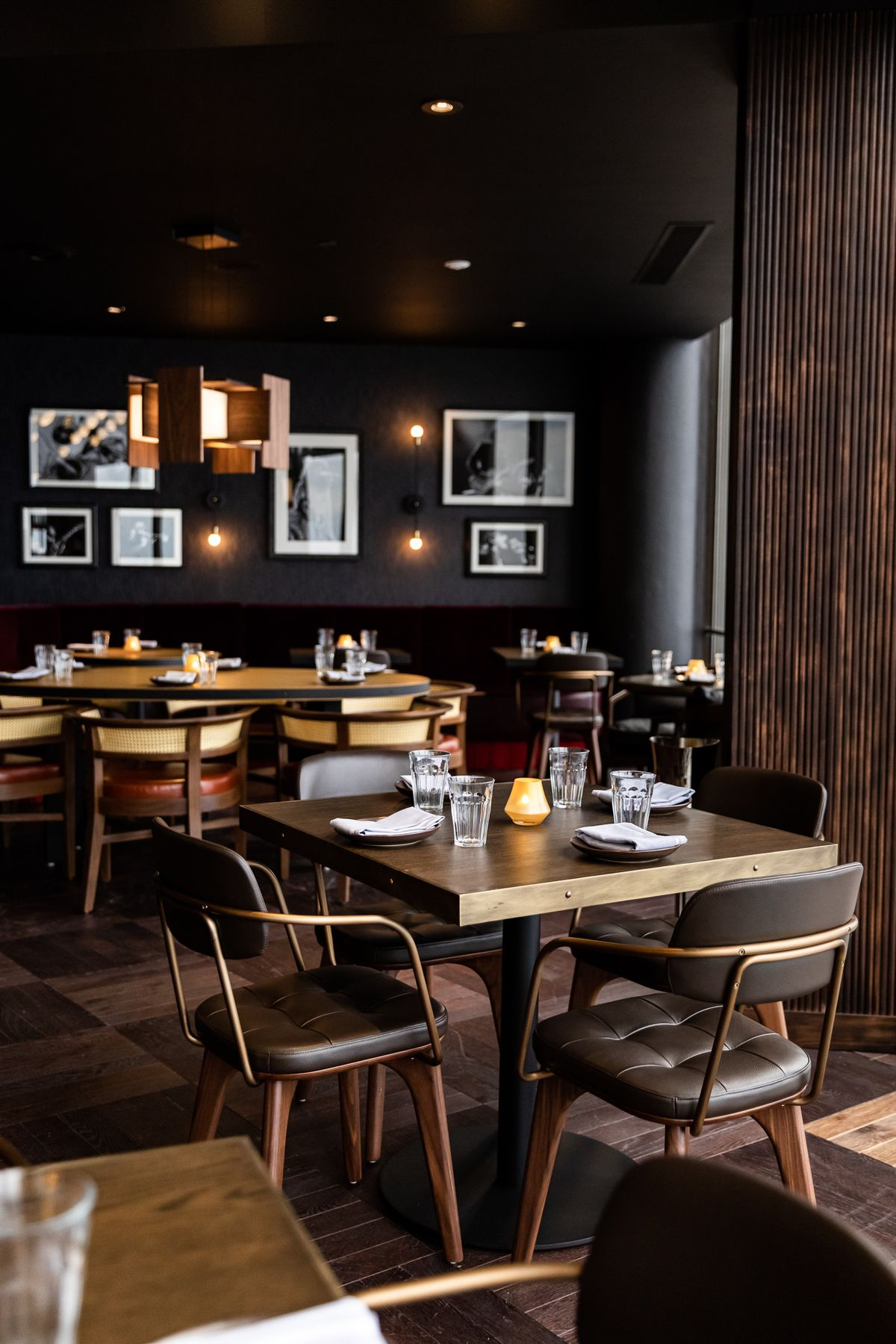 A black dining room with mid-century wood paneling and black and white photos on the walls.