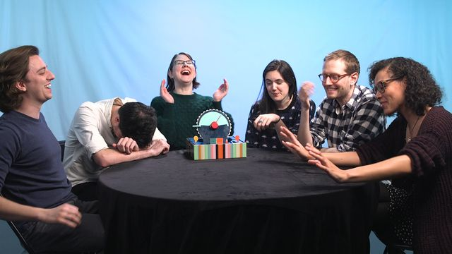 A group of board game players laughs while sitting around a table.