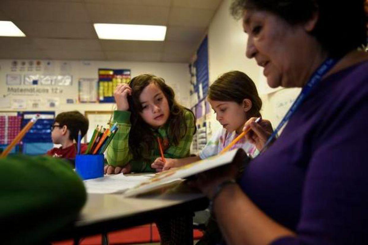Victoria Tisman, 8, left, works with paraprofessional Darlene Ontiveros on her Spanish at Bryant-Webster K-8 school in Denver.