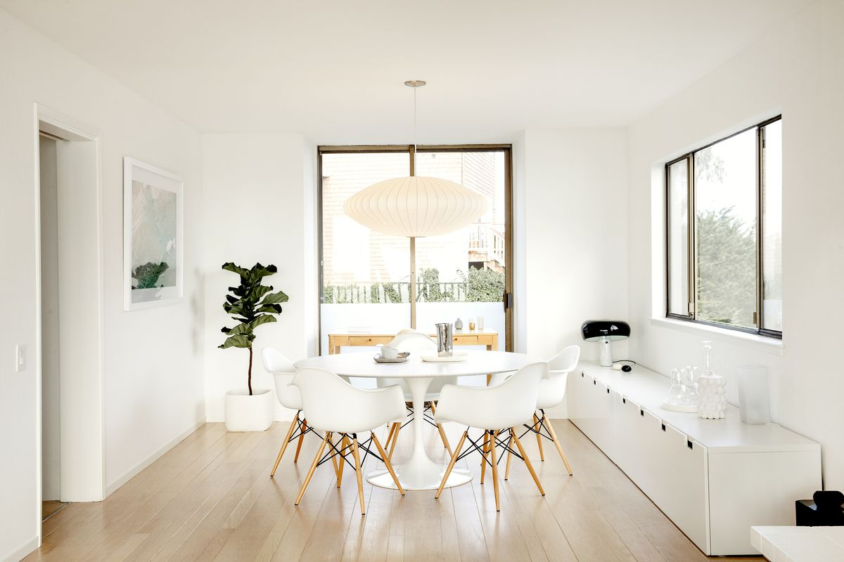The all white dining room, with sliding doors that lead outside and a large window.