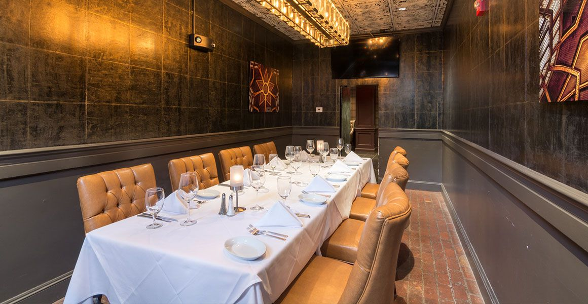 Ruth's Chris Steak House's Boston location's private room is long and narrow, with beige leather chairs and a brick floor.