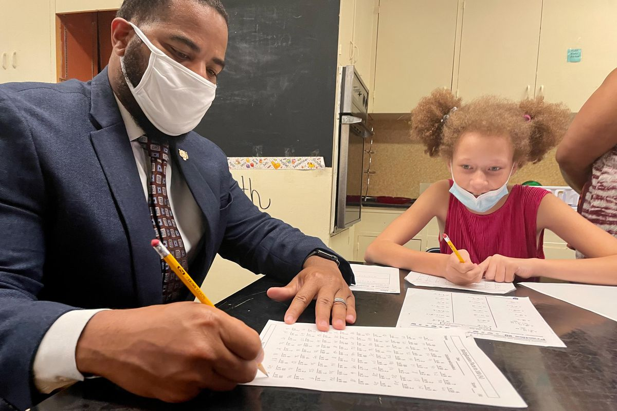 A male school administrator in a suit helps a girl with a multiplication worksheet, sitting with her at a desk. They are both wearing masks to prevent the spread of COVID.