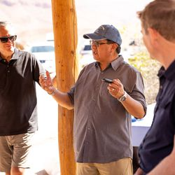 Manuel Heart, chairman of the Ute Mountain Ute Tribe, speaks to Sen. Mitt Romney, R-Utah, left, and Sen. Michael Bennet, D-Colo., after the group floated a section of the Colorado River northeast of Moab on Saturday, Sept. 18, 2021.