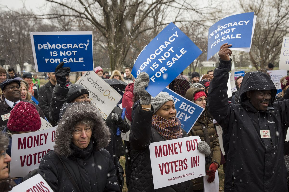 Attendees hold signs and cheer during a rally calling for an end to corporate money in politics and to mark the fifth anniversary of the Supreme Court's Citizens United decision, January 21, 2015.