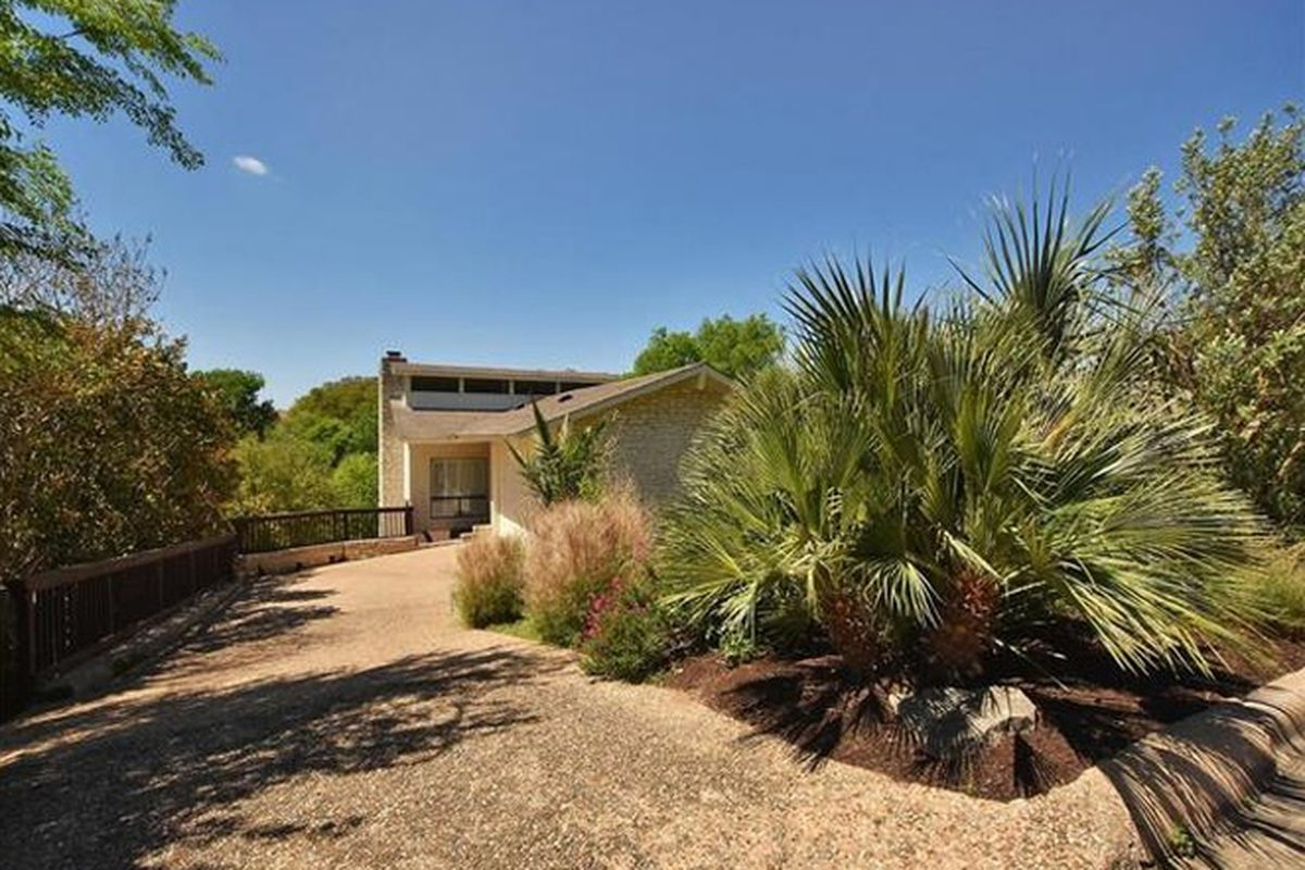 Short driveway lined with big palmetto and other plants leading to a 70s style house with chimney