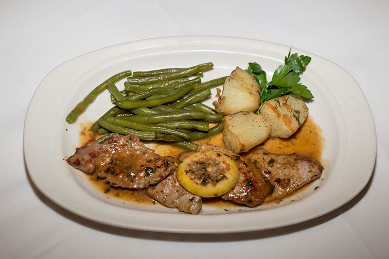 A plate of lamb with green beans and potatoes.