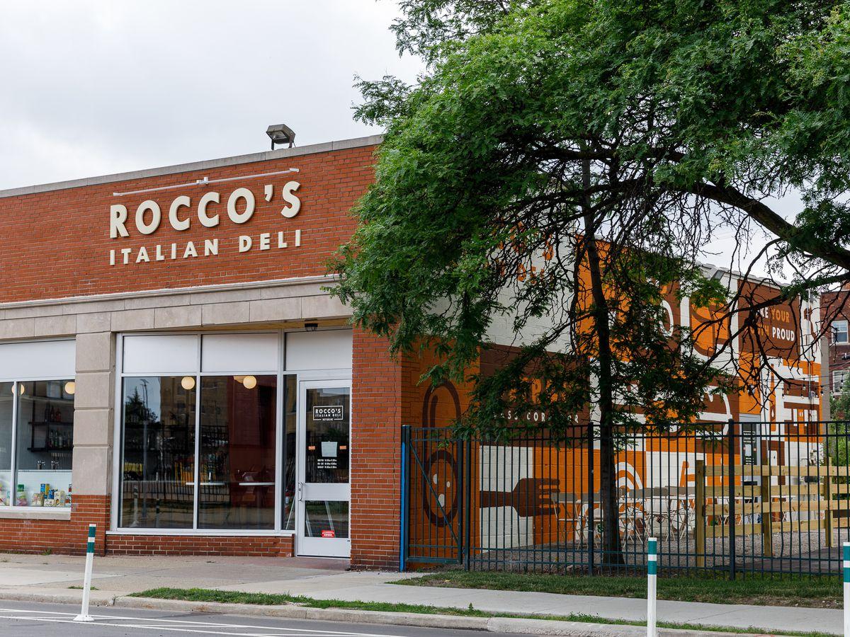 The brick exterior of Roccco's Italian Deli on a cloudy day.