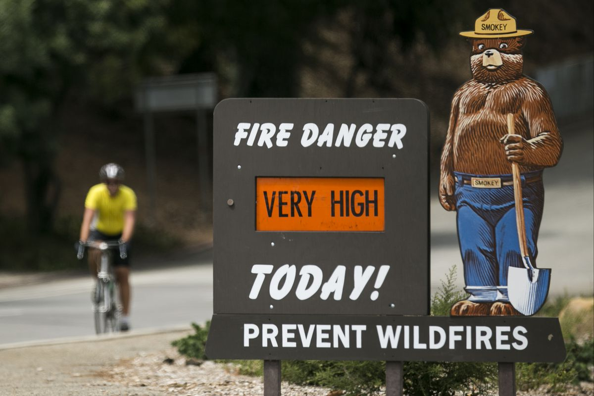 """A Smokey Bear """"Very High"""" fire danger sign is posted at the entrance to Griffith Park in Los Angeles."""