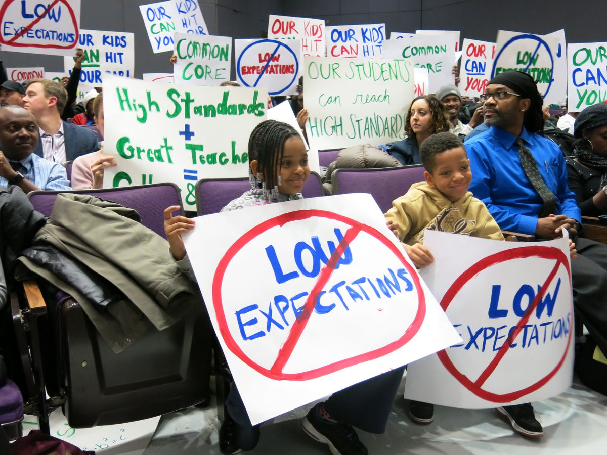 Supporters of the Common Core standards greeted State Education Commissioner John King at the forum in Brooklyn Tuesday. Many members of the parent advocacy group, StudentsFirstNY, arrived early to the meeting, snatched up many of the speaking slots and hoisted similar signs during the forum.