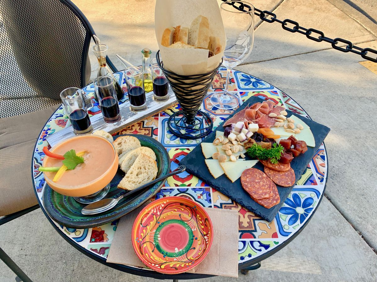 A BLUE PLATE WITH CHARCUTERIE, SMALL DIPS, AND SNACKS SITS NEXT TO A TRAY OF TASTING-SIZED POURS OF RED WINE.