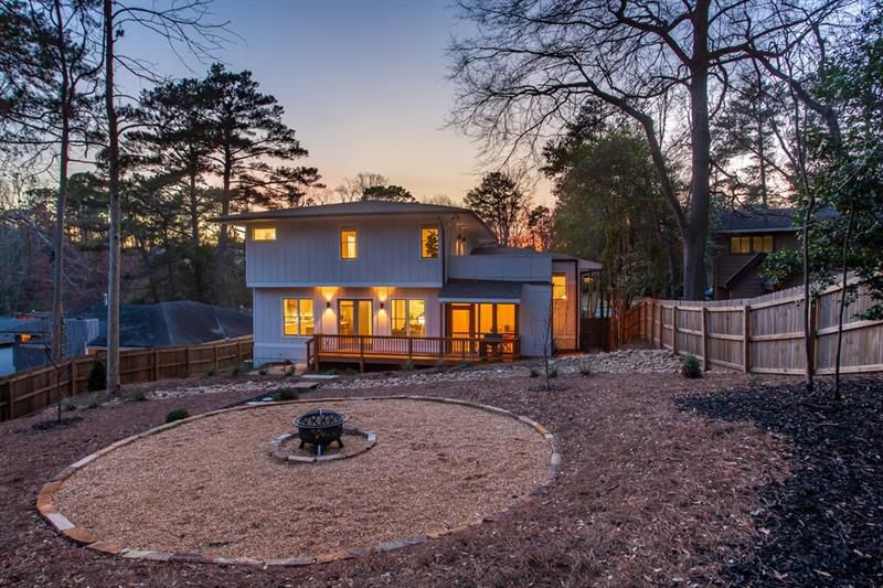 A sloping backyard with a huge fire pit area and a large gray house.