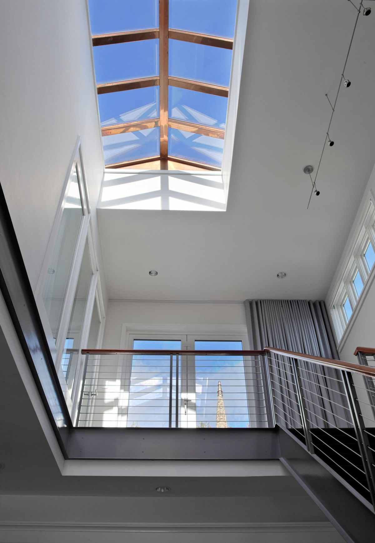 A view from a staircase looking up to a home's skylight.
