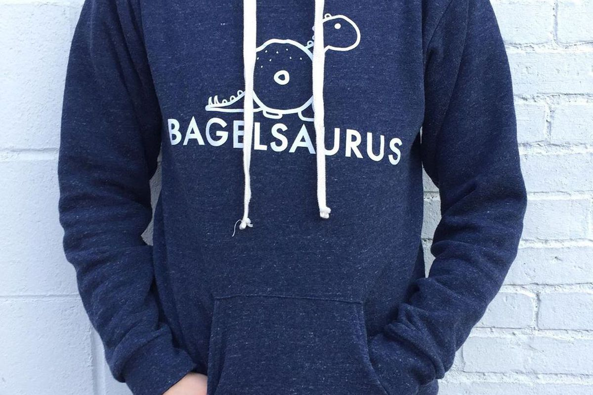 A navy hoodie sweatshirt with the logo for Bagelsaurus in Boston, featuring a sketch of a dinosaur made out of bagel shapes