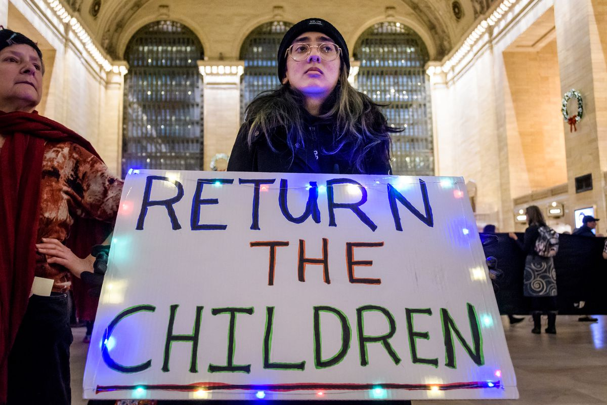 """The protester is holding a sign reading, """"Return the children."""""""
