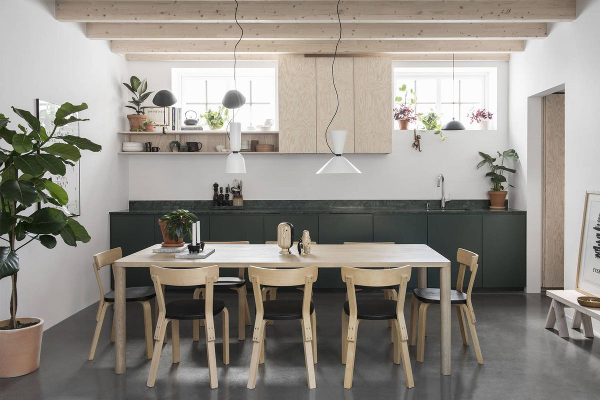Green cabinetry in kitchen with pale wood dining table.