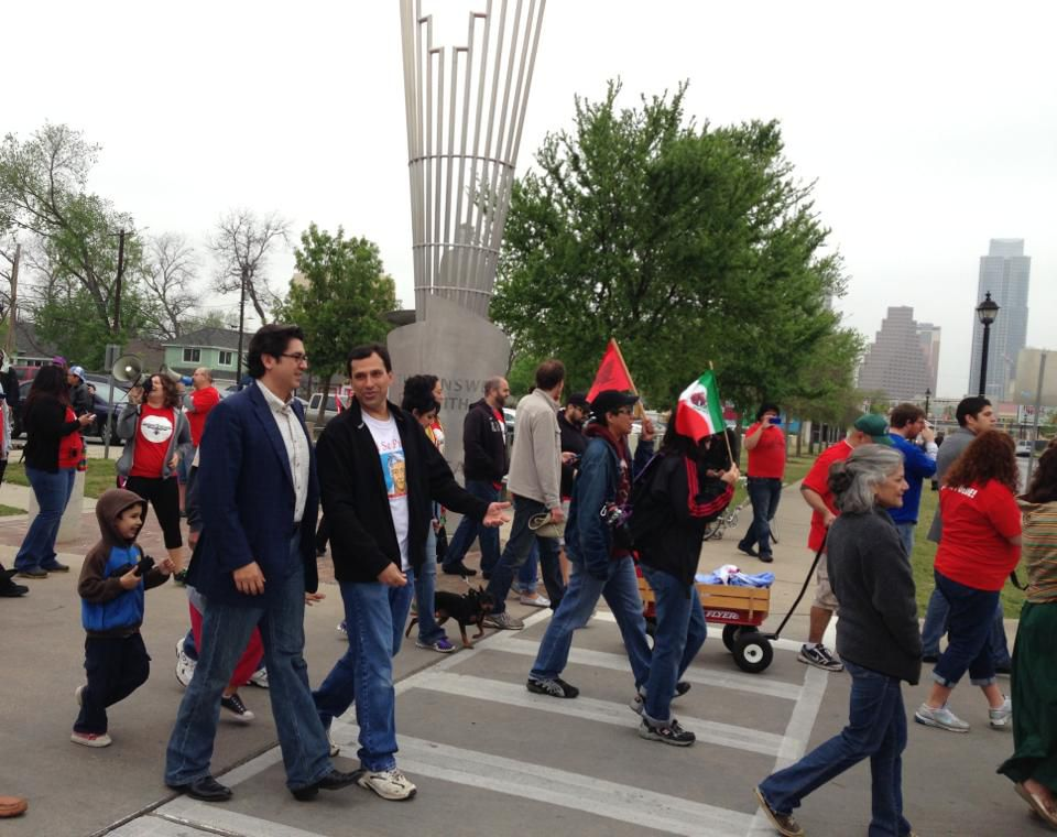 Group of marchers, some with Mexican flags and United Farmworkers flags and shirts with public sculpture and downtown buildings in background