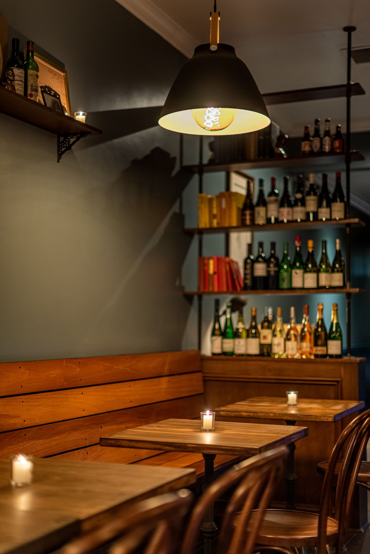 Vintage lighting and wooden tables at an old school wine bar.