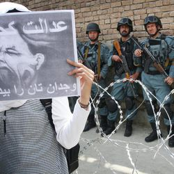 """An Afghan woman holds up a poster during a protest in Kabul, Afghanistan, Saturday, April 14, 2012. A group of Afghan women protested against domestic violence. The poster reads: """"Where is justice"""" and """"Wake up your conscience""""."""