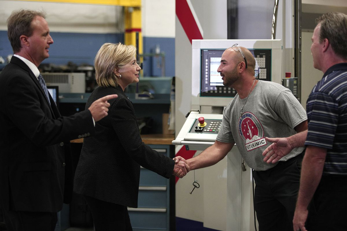 Hillary Clinton greets a worker at Futuramic Tool & Engineering, in Warren, Michigan, before a speech on the US economy.