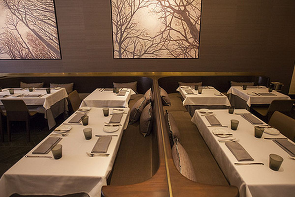 An upscale dining room with white tablecloths and art showing bare trees.