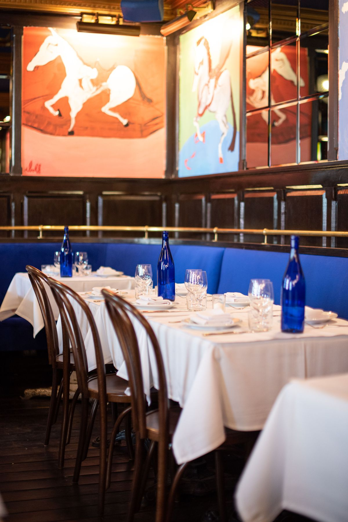 White tablecloths and blue booths and hanging paintings in an old restaurant.