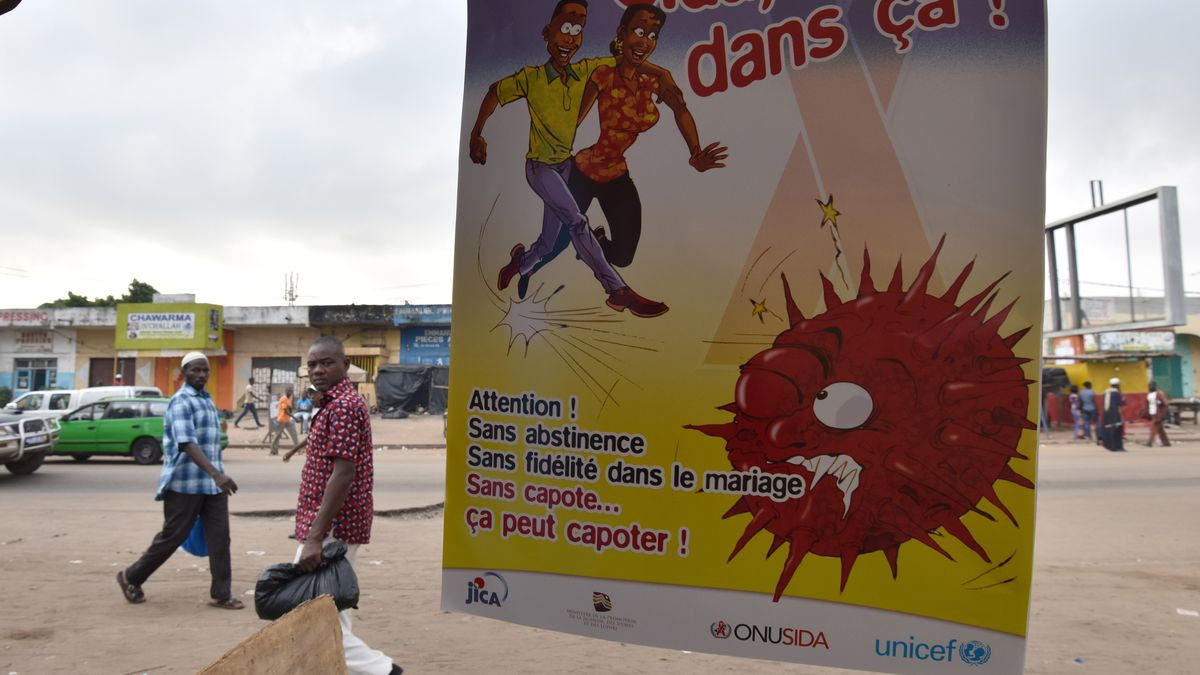 A man walks by a public health poster in Abidjan, Côte d'Ivoire. (Sia Kambou/AFP/Getty Images)