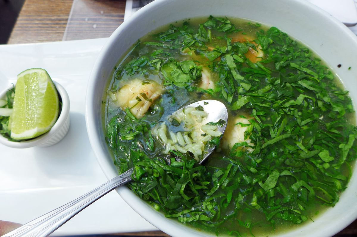 A big green soup with a lime wedge on the side.