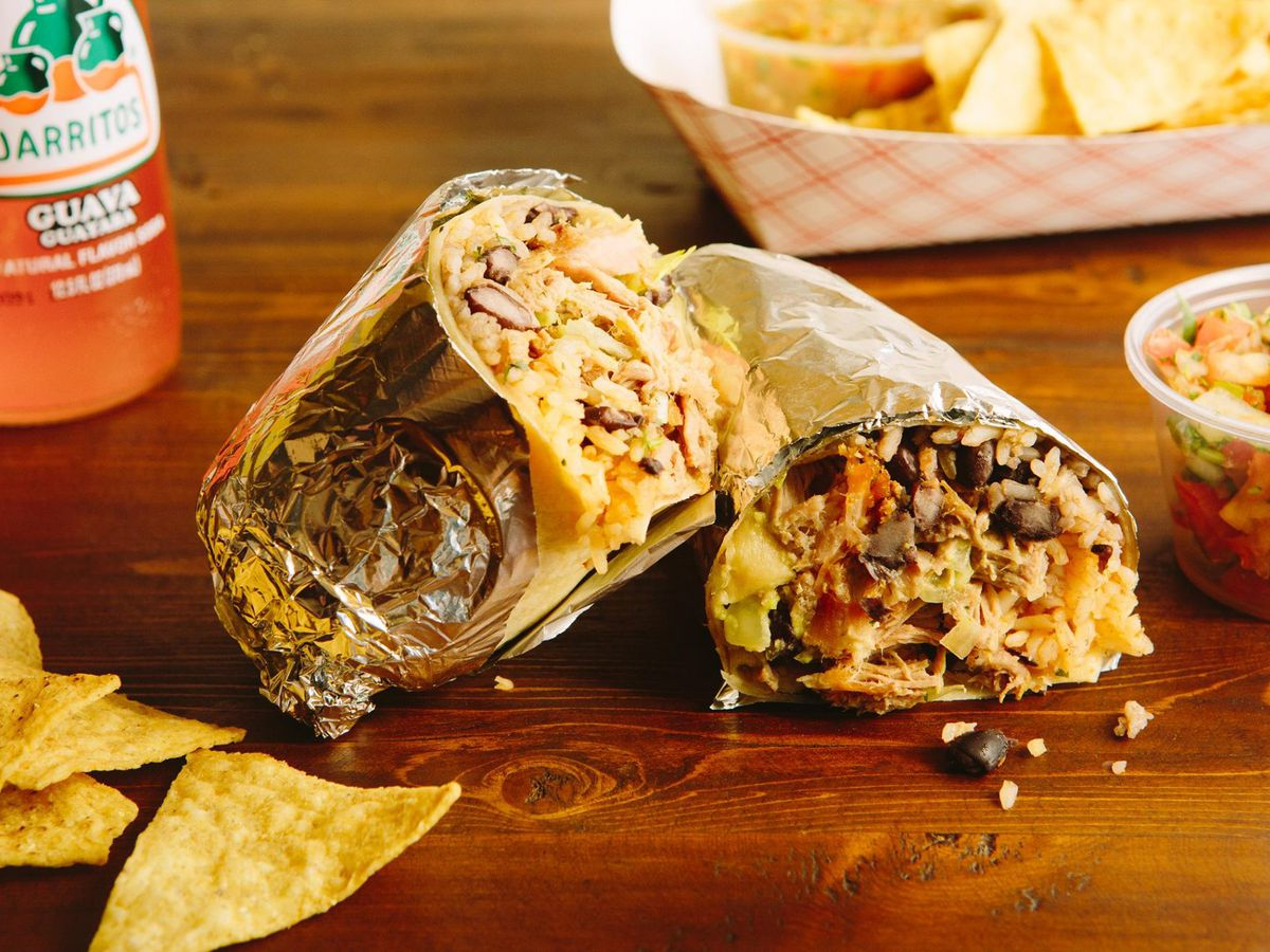 A burrito, split in half and wrapped in foil, sits on a wooden table with a side of salsa and tortilla chips nearby. An orange Jarritos soda bottle is visible in the background.