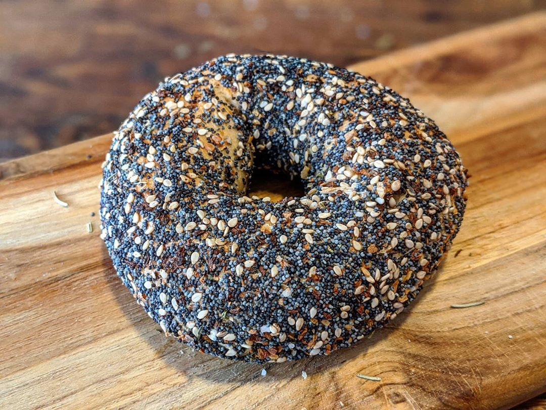 Closeup of an everything bagel, very covered with poppyseeds and sesame seeds, on a small wooden plank sitting on a wooden countertop