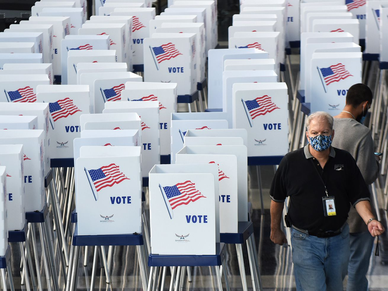 An election worker in a mask stands beside voting booths at an early voting location in Florida.