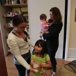 In this Sept. 26, 2012 picture, Sabina Widmann, right, holds her baby girl Stella while domestic worker Alicia Wotherspoon, left, helps her daughter Luna with a glass of water before work at their home in San Diego.