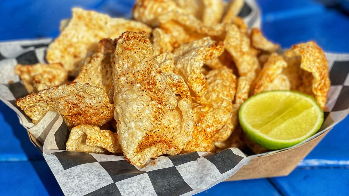 A brown paper basket of fried pork skins served with a lime. The pork skins are sitting on top of black-and-white checkered paper.